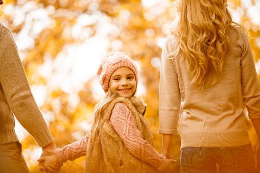 658444674 istock photo Walking with parents in autumn park 610235476