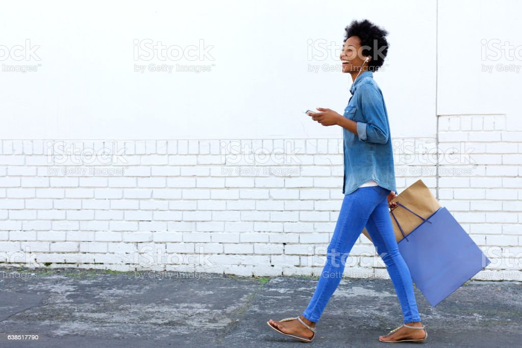 Walking with shopping bags and listening to music stock photo