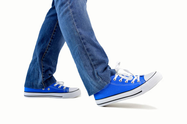 walking with sneakers close up of steps of a person walking with sneakers and jeans isolated on white background stepping stock pictures, royalty-free photos & images