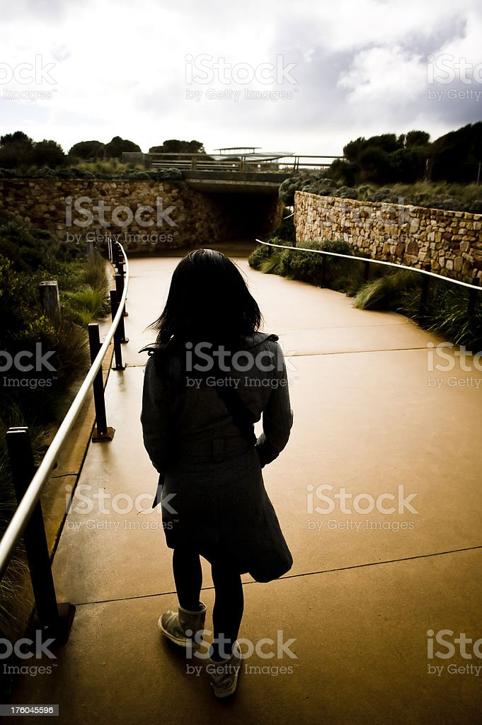 Walking woman down cement path with photo taken from behind royalty-free stock photo