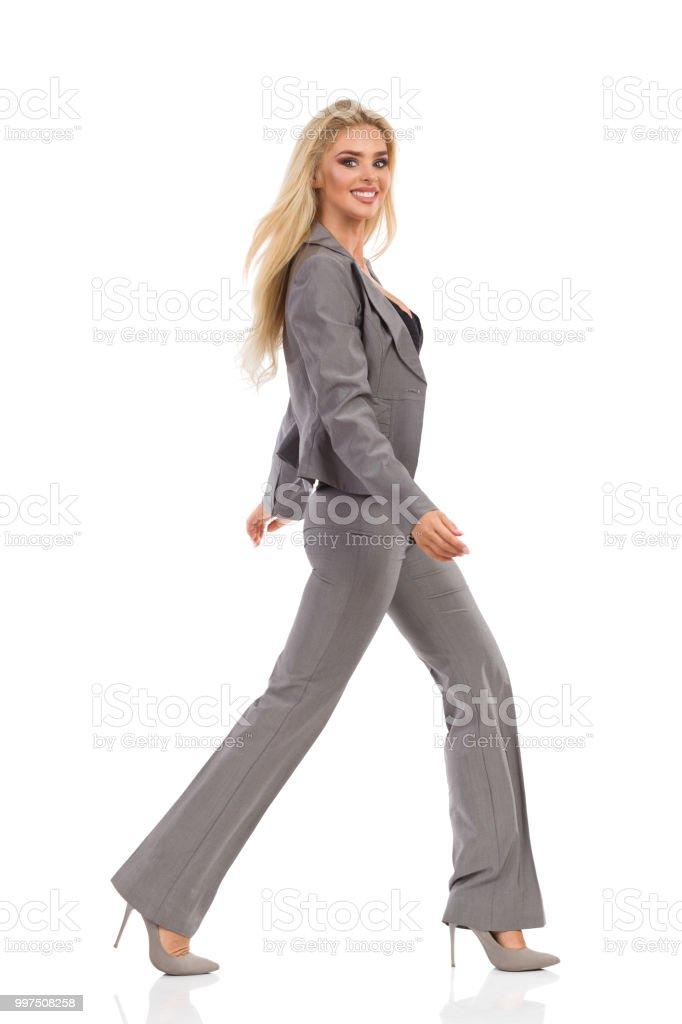 Poca mujer en traje gris está sonriendo y mirando a cámara foto de stock  libre de 19dae7e29d85