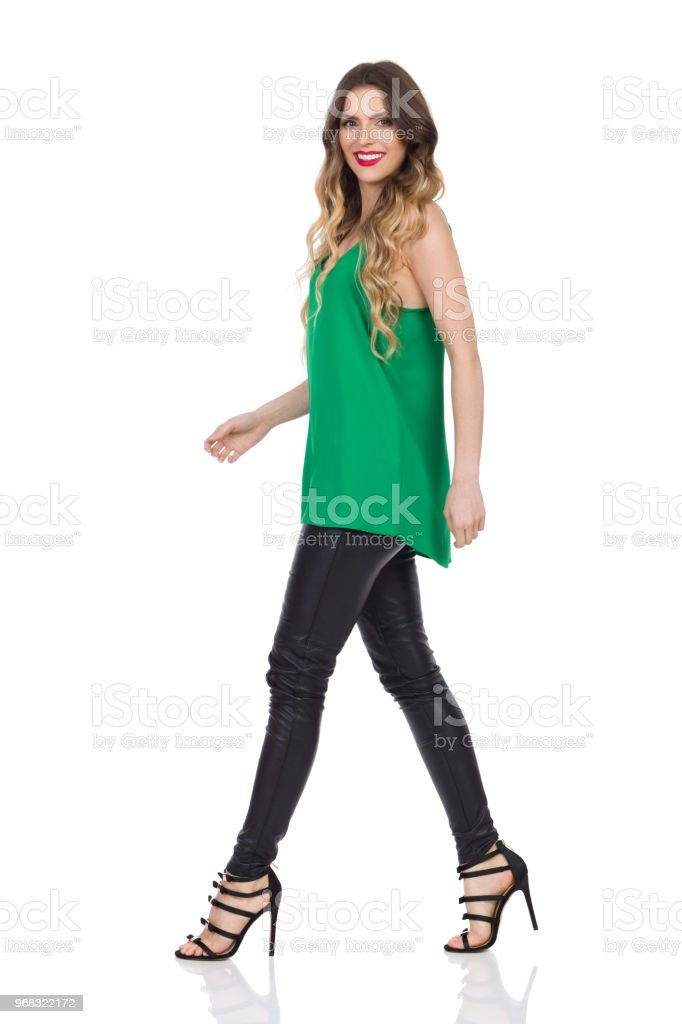faa08f3c8da Walking Woman In Leather Trousers And High Heels Looking At Camera ...