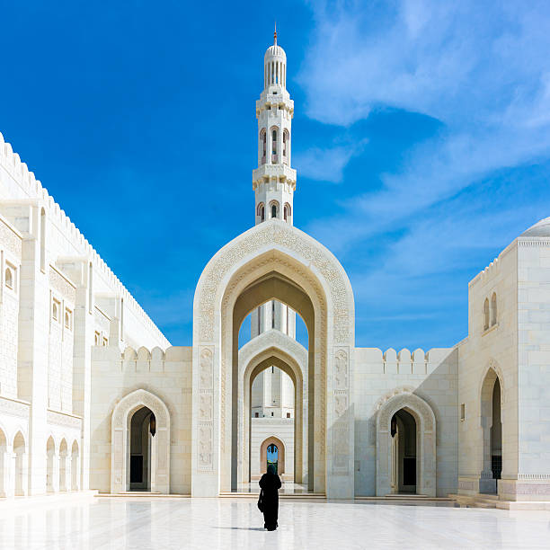 Walking Woman in Sultan Qaboos Grand Mosque Muscat Oman Woman in black Abaya Gown walking towards the giant arch in the famous Sultan Qaboos Grand Mosque in Muscat, Oman, Middle East, Arabia. grand mosque stock pictures, royalty-free photos & images