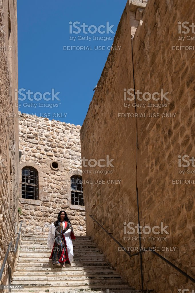 Walking woman in traditional clothes, Mardin stock photo
