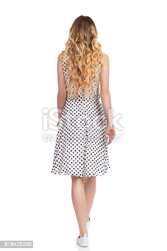 Young woman in white dotted dress, sneakers is walking. Rear view. Full length studio shot isolated on white.