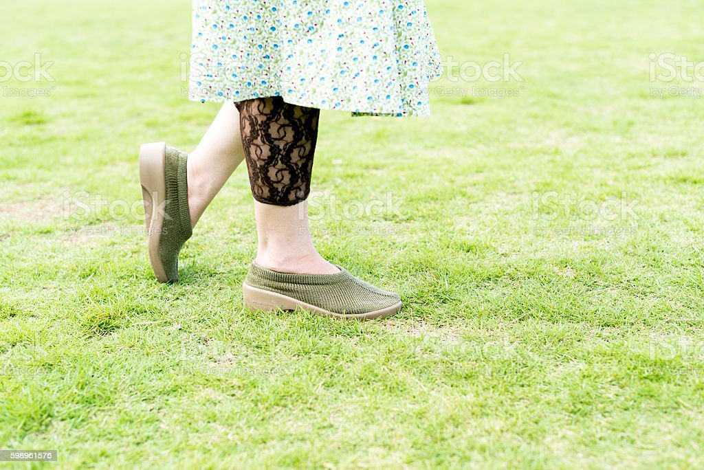 Walking woman on the green field stock photo