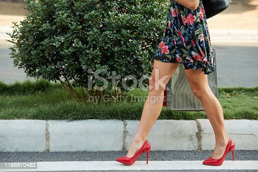 Beautiful legs of young woman in short floral summer dress and bright red heels walking on pavement