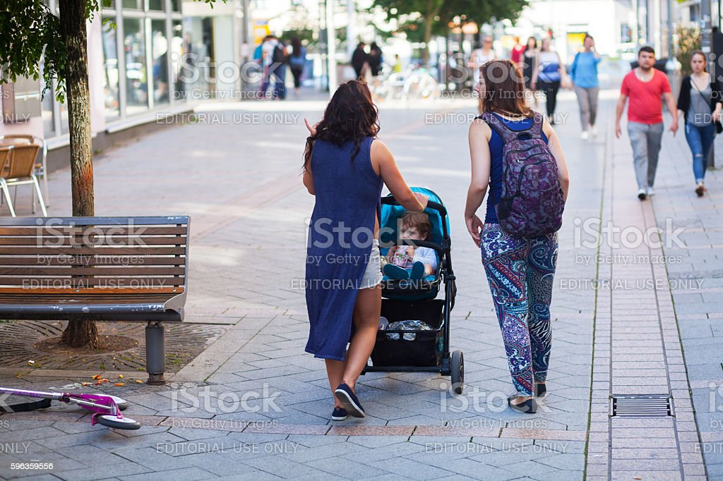 Walking women with baby buggy and child royalty-free stock photo
