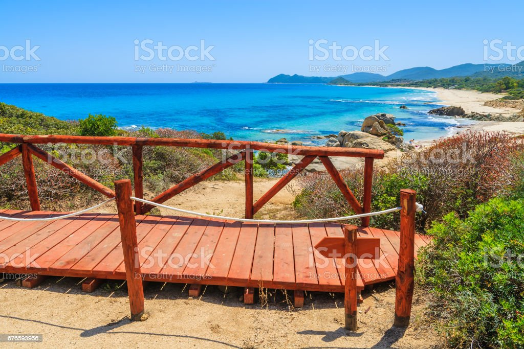 Walking wooden platform at Cala Sinzias bay and turquoise sea view, Sardinia island, Italy stock photo
