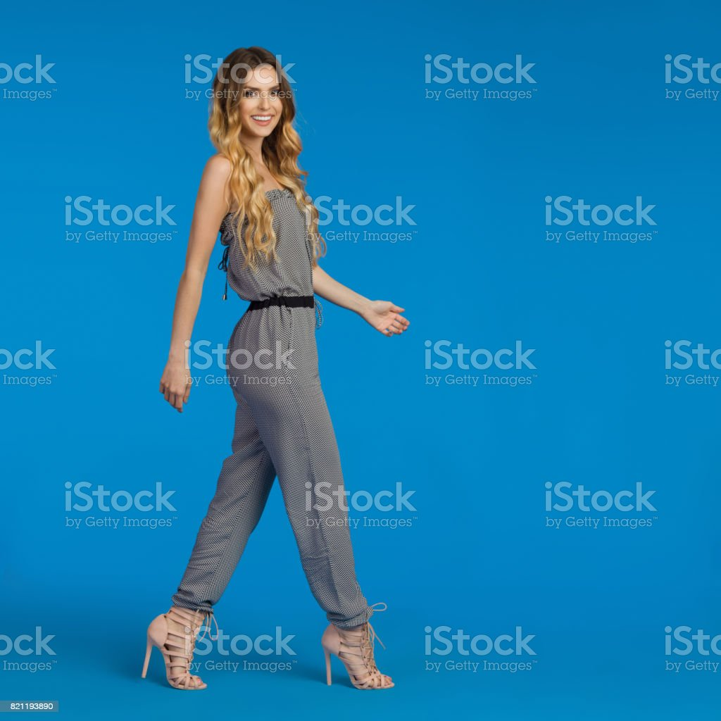Walking Young Woman In Jumpsuit And High Heels stock photo
