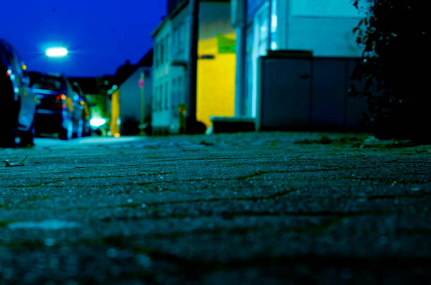 Walkway in a city with a narrow focus on the cobblestones and downtown out of focus in the background, shallow focus gradient and blue, cold colors with yellow. Walkway in a city with a narrow focus on the cobblestones and downtown out of focus in the background, shallow focus gradient and blue, cold colors with yellow. ambush stock pictures, royalty-free photos & images