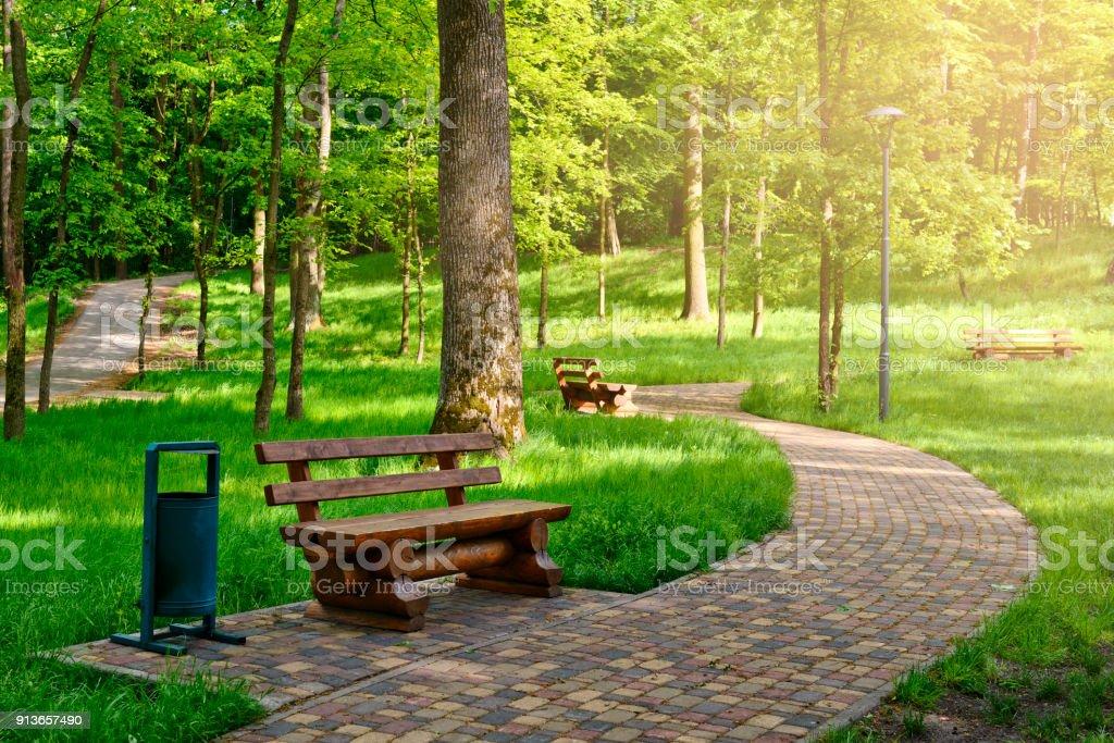 Promenade dans un parc de printemps ensoleillé avec des bancs en bois pour reste - Photo