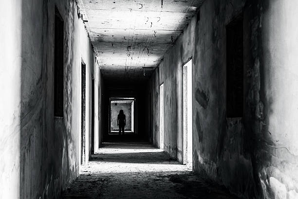 walkway in abandoned building with scary woman inside stock photo
