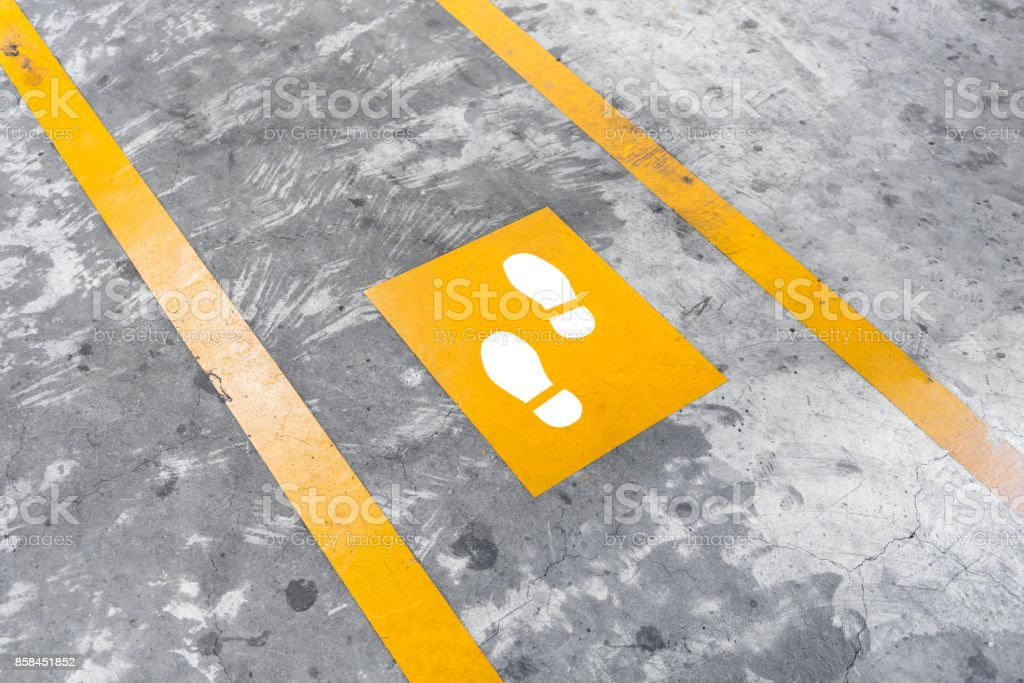 Walkway lane in parking building. Painted yellow footsteps between parallel yellow lines on abstract cement floor. stock photo