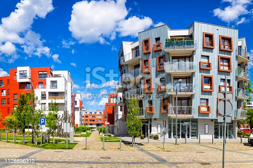 889473004 istock photo Walkway leading along the new colorful complex of apartment buildings 1128896312