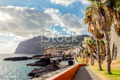 Walkway to small fishing village Camara de Lobos on Madeira Island. Sea cliff Cabo Girão in the distance, palm trees growing by the sidewalk, coast with Atlantic ocean water. Tourism concept.