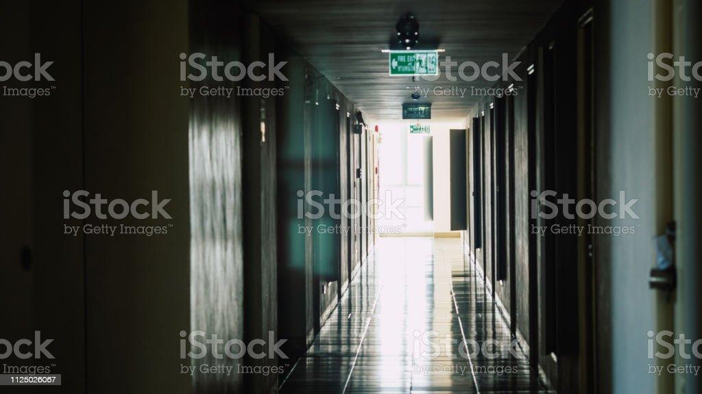 Walkway to the fire escape door, Fire exit sign over corridor walkway...