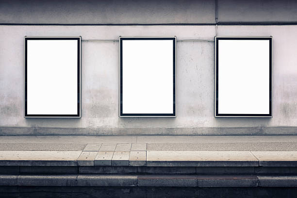 Wall advertising Three blank posters on a wall by a station platform. Includes clipping paths. subway platform stock pictures, royalty-free photos & images