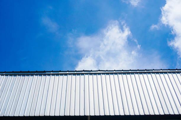 wand und dach werk oder lager gebäudes unter blauem himmel mit wolken - alu zaun stock-fotos und bilder
