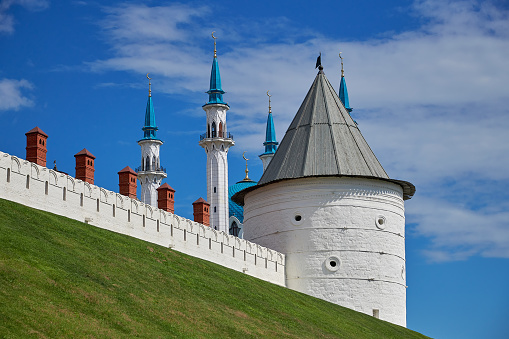 Wall and white tower of the Kazan Kremlin. Behind the tower are visible minarets of the mosque.