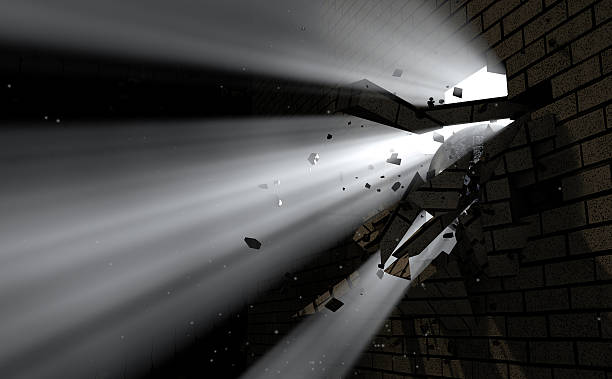 Wall Break Through And Light A dark side of a wall being broken and shattered by a wrecking ball with light emanating through emergence stock pictures, royalty-free photos & images