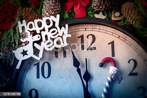1030268332 istock photo Wall clock in Christmas or New Year decorations are wrapped with fir branches and Christmas decorations. On the clock five minutes to midnight. 1078108706