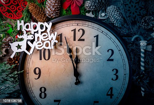 1030268332 istock photo Wall clock in Christmas or New Year decorations are wrapped with fir branches and Christmas decorations. On the clock five minutes to midnight. 1078108758