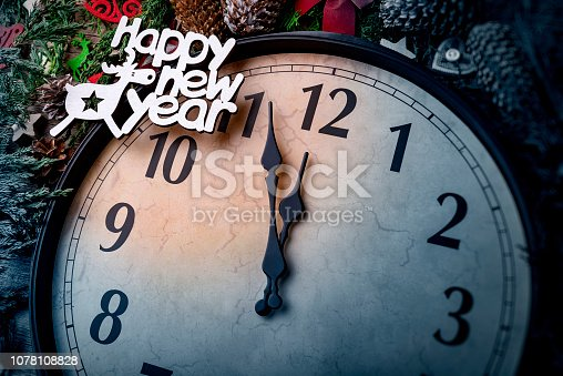 1030268332 istock photo Wall clock in Christmas or New Year decorations are wrapped with fir branches and Christmas decorations. On the clock five minutes to midnight. 1078108828
