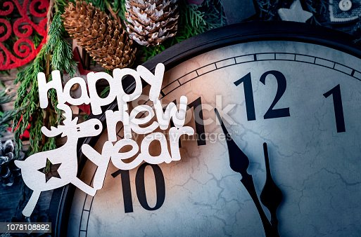 1030268332 istock photo Wall clock in Christmas or New Year decorations are wrapped with fir branches and Christmas decorations. On the clock five minutes to midnight. 1078108892