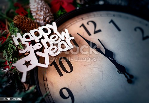 1030268332 istock photo Wall clock in Christmas or New Year decorations are wrapped with fir branches and Christmas decorations. On the clock five minutes to midnight. 1078108956