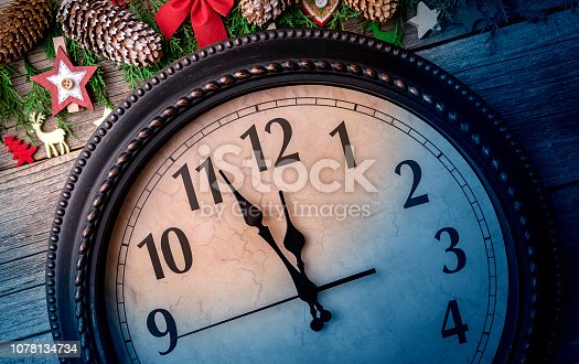 1030268332 istock photo Wall clock in Christmas or New Year decorations are wrapped with fir branches and Christmas decorations. On the clock five minutes to midnight. 1078134734