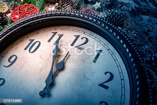 1030268332 istock photo Wall clock in Christmas or New Year decorations are wrapped with fir branches and Christmas decorations. On the clock five minutes to midnight. 1078134892