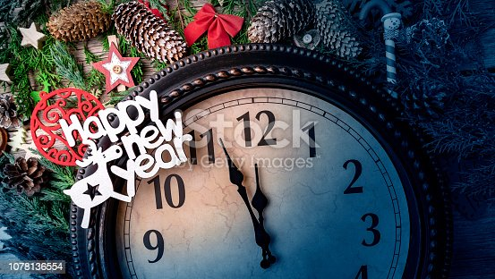 1030268332 istock photo Wall clock in Christmas or New Year decorations are wrapped with fir branches and Christmas decorations. On the clock five minutes to midnight. 1078136554