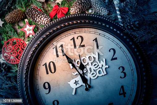 1030268332 istock photo Wall clock in Christmas or New Year decorations are wrapped with fir branches and Christmas decorations. On the clock five minutes to midnight. 1078136866