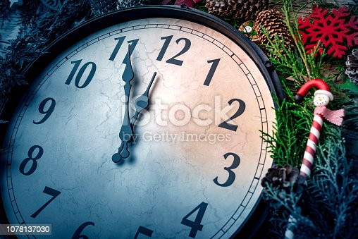 1030268332 istock photo Wall clock in Christmas or New Year decorations are wrapped with fir branches and Christmas decorations. On the clock five minutes to midnight. 1078137030