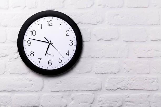 reloj de pared en pared de ladrillo blanco - wall clock fotografías e imágenes de stock