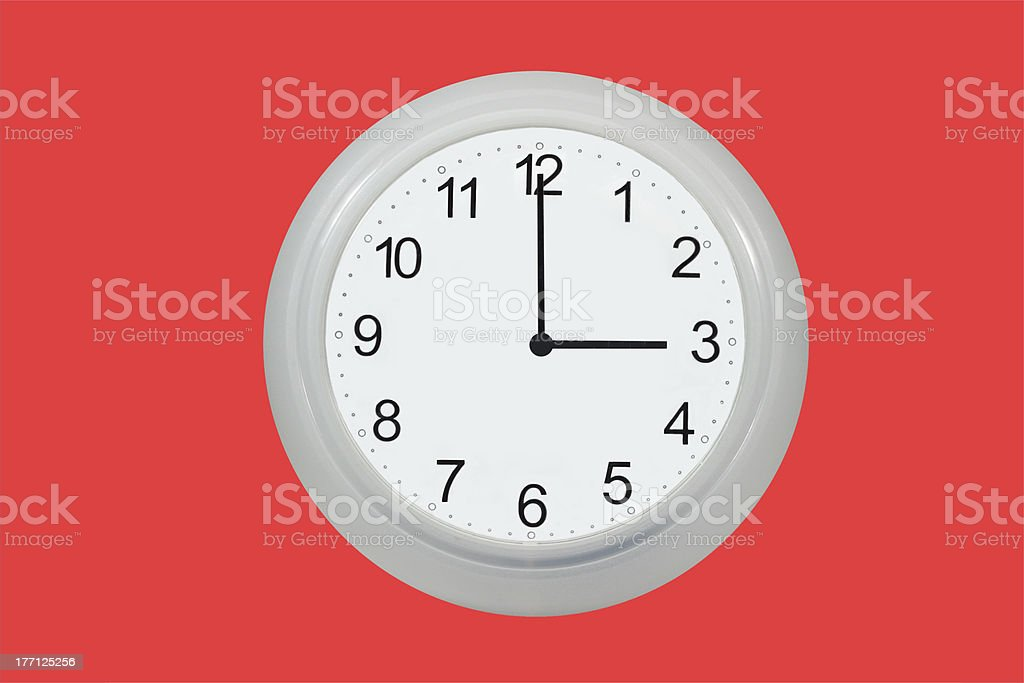 Wall clock showing 3 o'clock isolated on red royalty-free stock photo