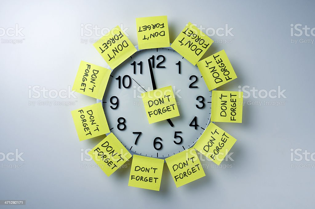 Wall clock with 'don't forget' notes all over stock photo