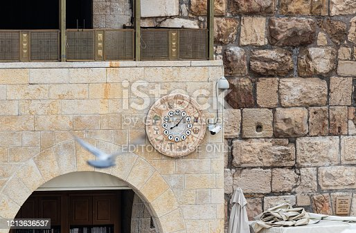 Jerusalem, Israel, March 3, 2020 : Wall clock with the designation of 12 Jewish tribes hang on the wall near the Western Wall near the Dung Gate in Jerusalem in Israel