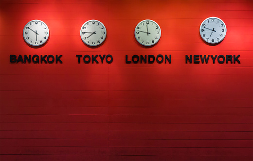 4 wall clocks on red wooden panel, show different time of world capital city. ( Bangkok, tokyo, london, newyork)