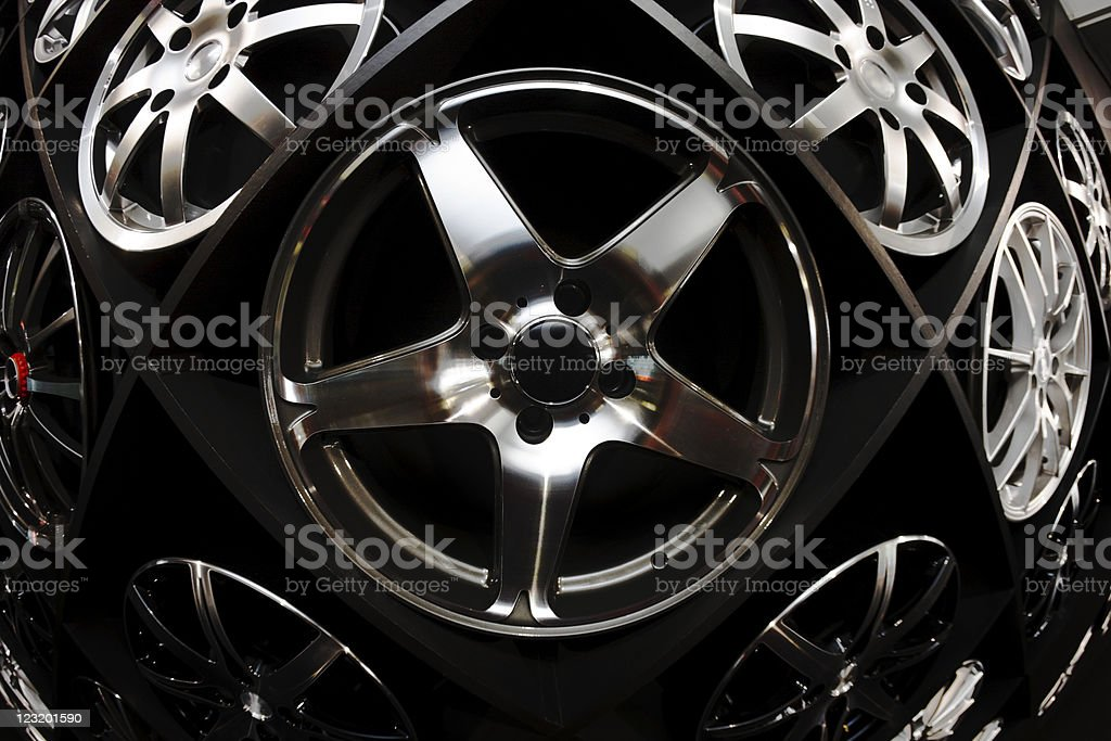 Wall display of automobile wheels, shot with fisheye lens. stock photo
