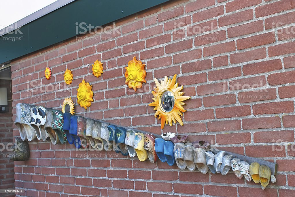 Wall dutch house  decorated old shoes and sun. Netherlands royalty-free stock photo