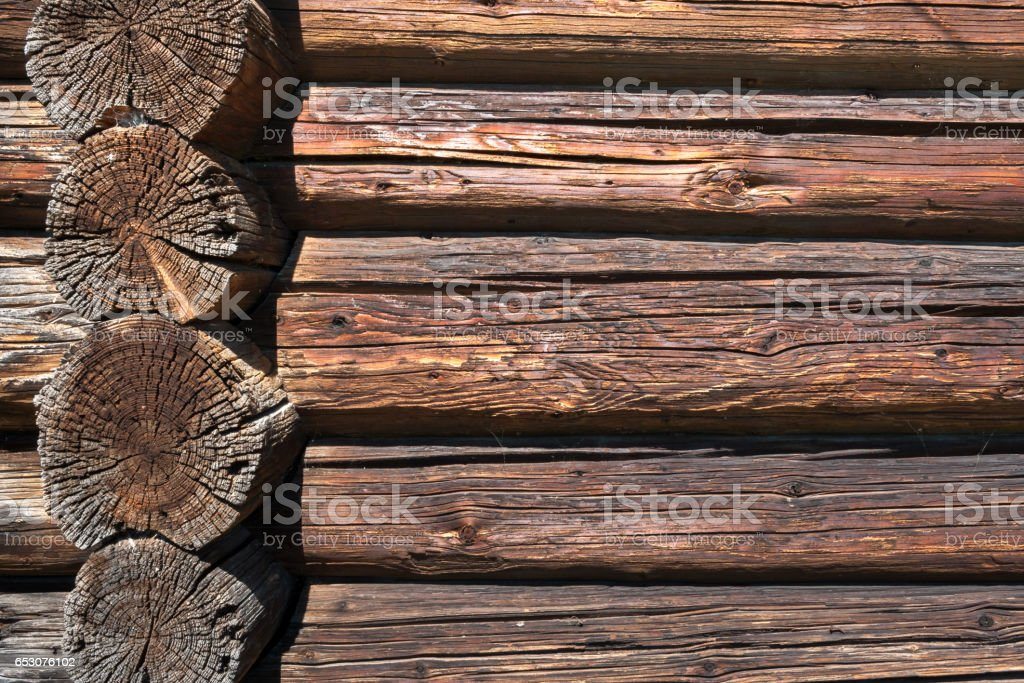 Wall from old dilapidated longitudinal and transverse logs. stock photo