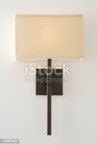 A wall lamp (sconce) with the light on mounted on a white wall.
