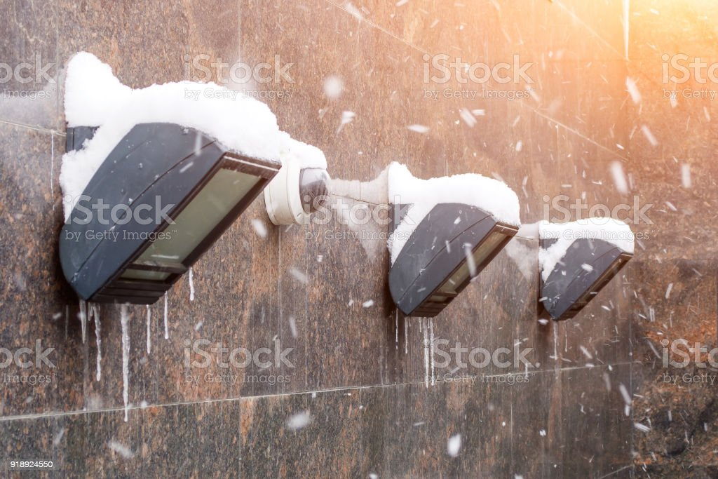 Wall lighting lanterns covered with snow with icicles from ice, and a video camera. stock photo