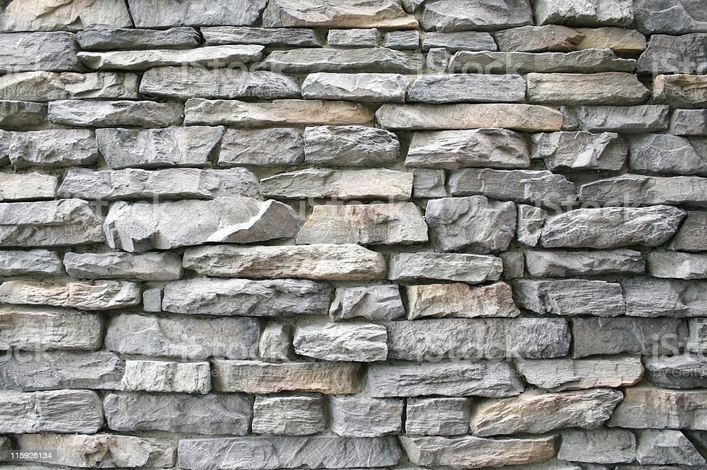 Wall made of gray and rectangular stones stock photo