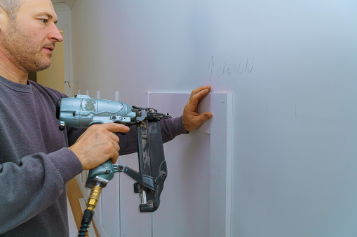 istock Wall moulding trim air gauge finish nailer man nailed custom house building contractor 1089679364
