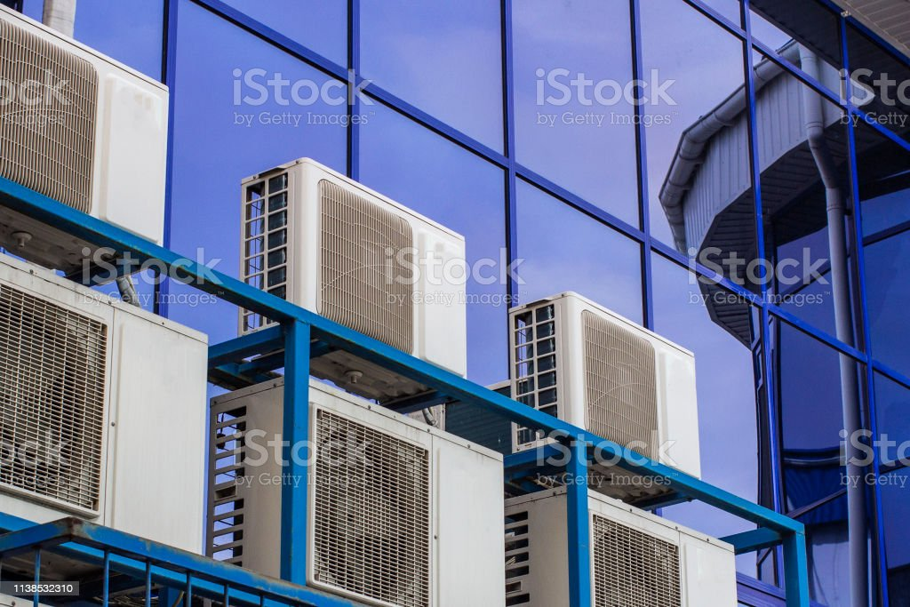 Wall of a large office building with blue windows and air conditioning