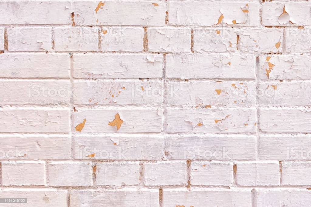 A wall of bricks of different sizes. The surface is painted light...