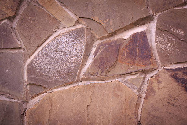 Wall of colorful old flagstone with rough wide cement joints. Toned patterned background stock photo